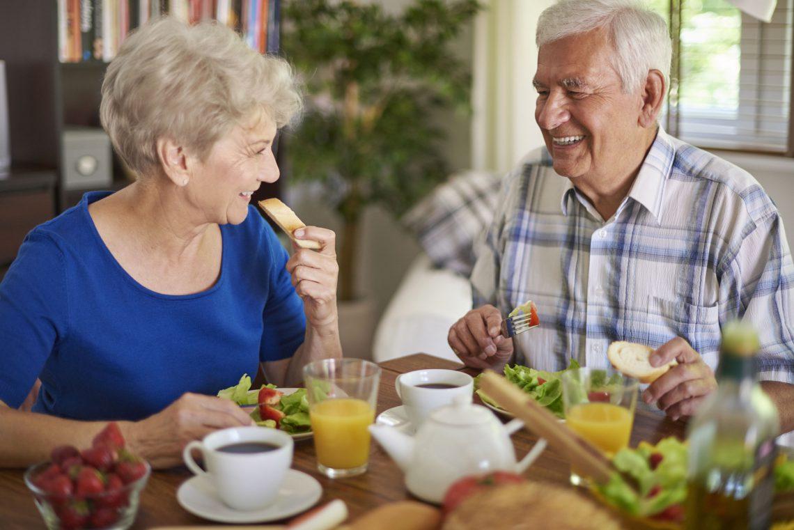 Elderly couple eating breakfast