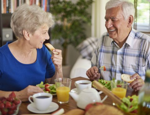 Elderly couple eating breakfast